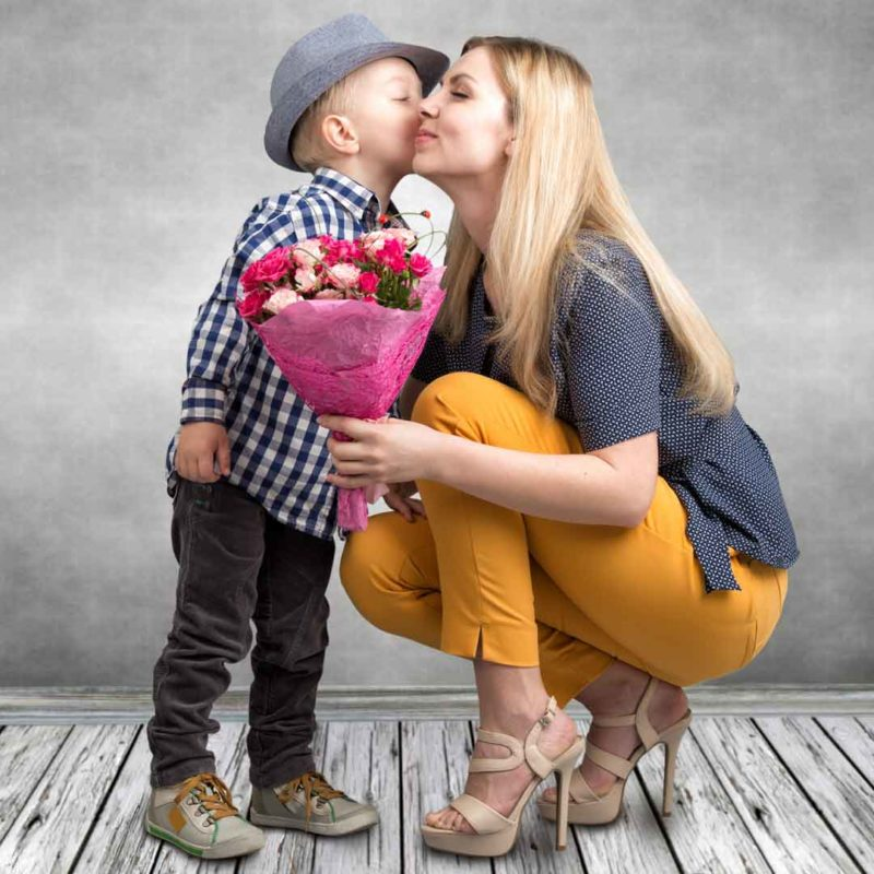 Adorable photo of mother getting flowers from her young son